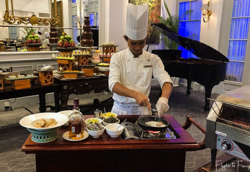 Chef at Le Royal Restaurant at Raffles Hotel Phnom Penh cooking scallops at our table